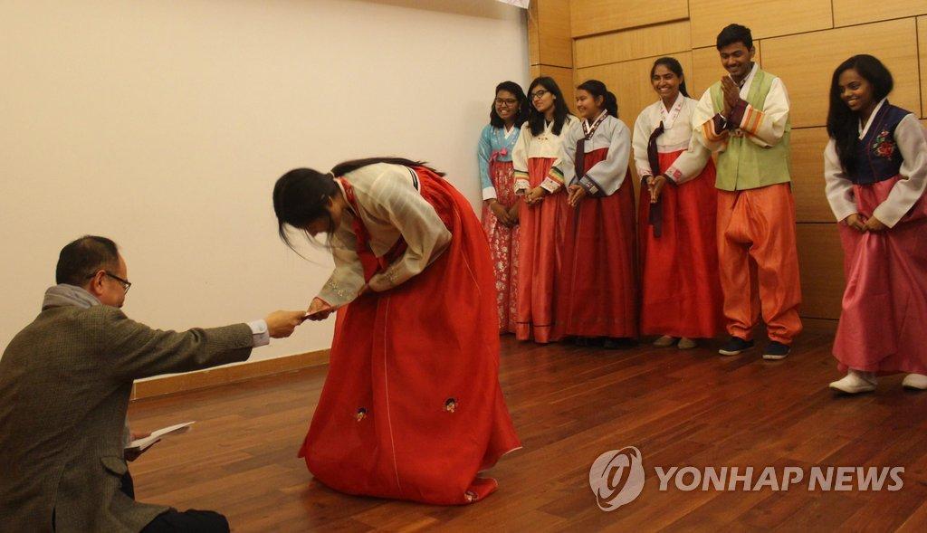 资料图片:外国留学生拜年收钱喜洋洋。(韩联社)