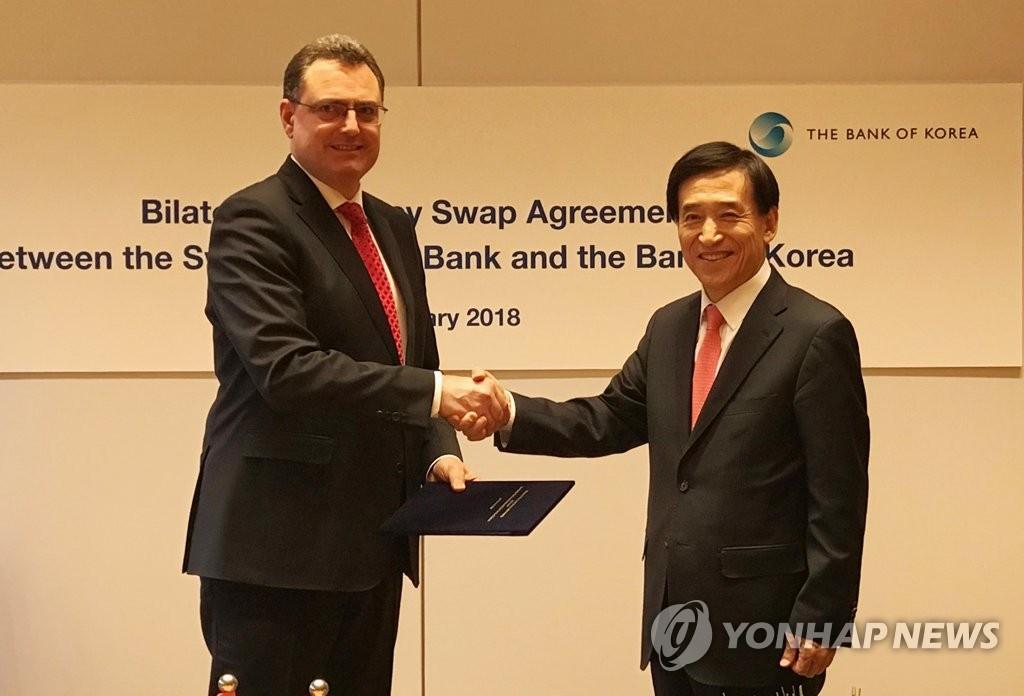 当地时间2月20日,在瑞士央行总部,李柱烈(右)和乔丹在签字仪式结束后握手合影。(韩联社/韩国银行提供)
