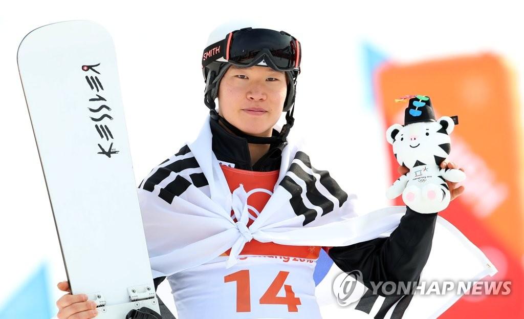 2月24日,在江原道平昌凤凰雪上公园,韩国单板滑雪运动员李相昊在领奖台上摆姿势接受媒体拍照。(韩联社)