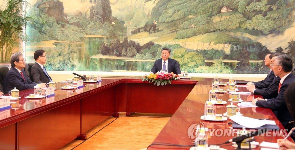 3月12日下午,在北京人民大会堂,中国国家主席习近平(左三)接见韩国总统文在寅特使、青瓦台国家安保室长郑义溶(左二)。(韩联社)
