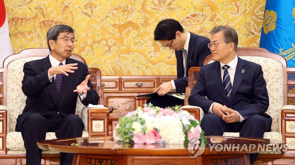3月14日,在青瓦台,韩国总统文在寅(右)会见亚洲开发银行行长中尾武彦。(韩联社)