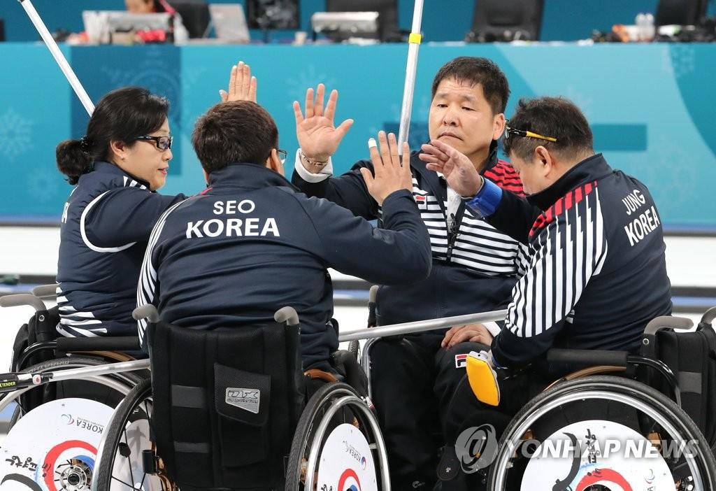 3月16日,在江陵冰球中心,韩国队在2018平昌冬残奥会轮椅冰壶半决赛中以6:8输给挪威队。图为韩国队击掌鼓舞士气。(韩联社)