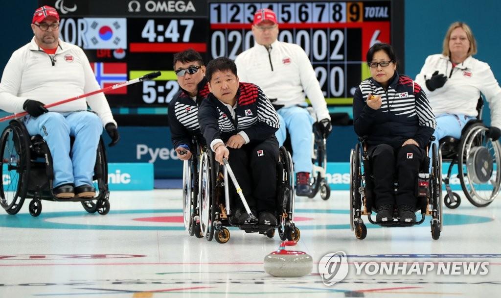3月16日,在江陵冰球中心,韩国队在2018平昌冬残奥会轮椅冰壶半决赛中以6:8输给挪威队。图为韩国队推出冰壶。(韩联社)