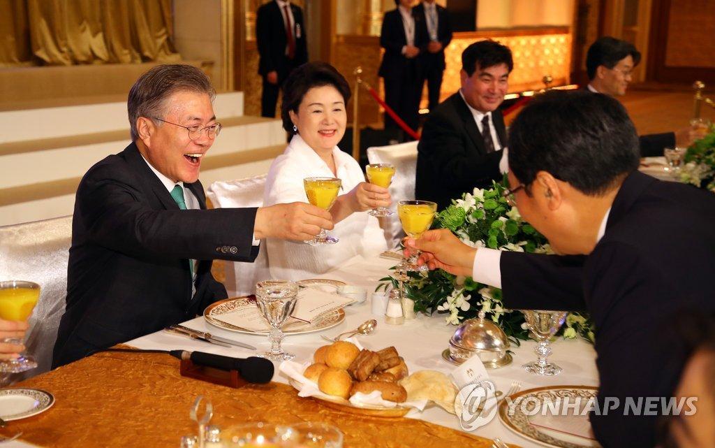 当地时间3月25日,在阿布扎比一家酒店,文在寅(左)在侨胞座谈会上举杯。(韩联社)
