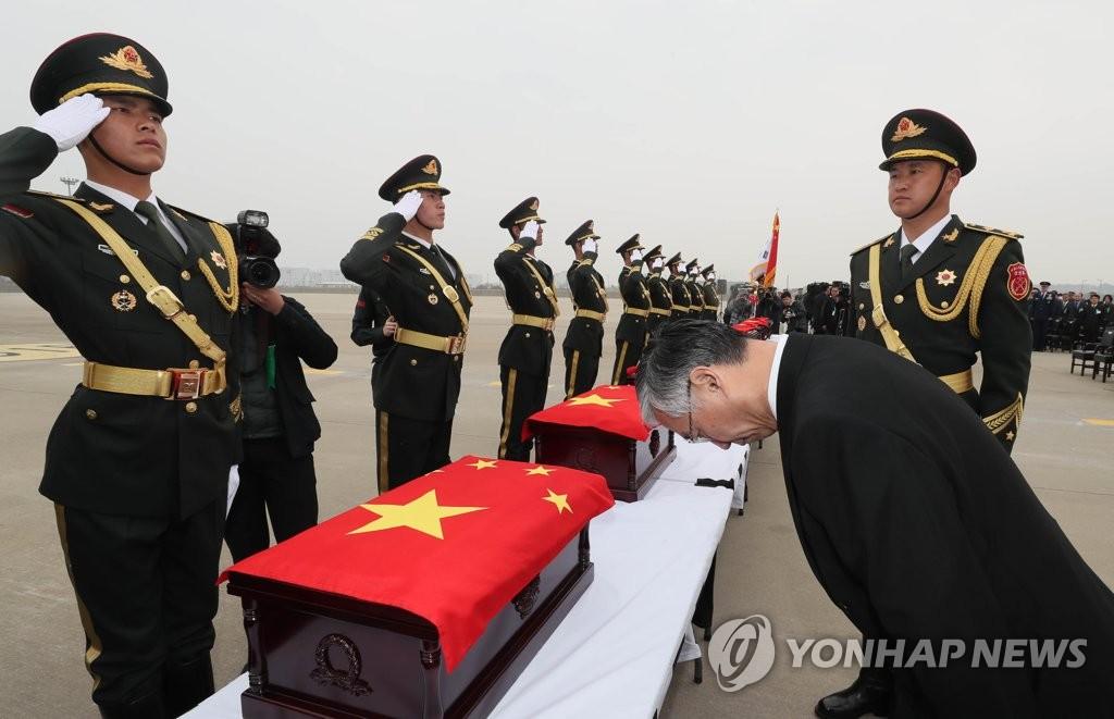 邱国洪向中国军人遗骸鞠躬致敬