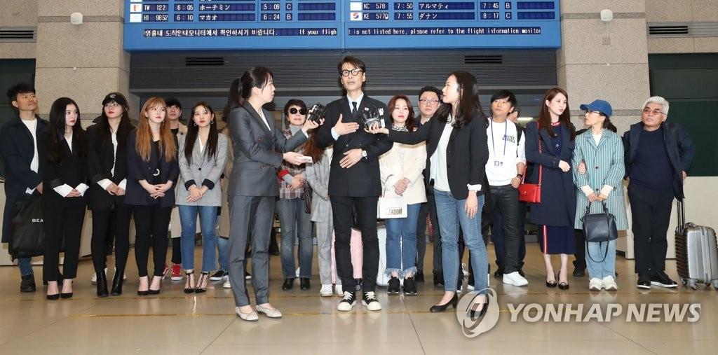 4月4日凌晨,在仁川国际机场,韩国艺术团抵韩后接受媒体采访。(韩联社)