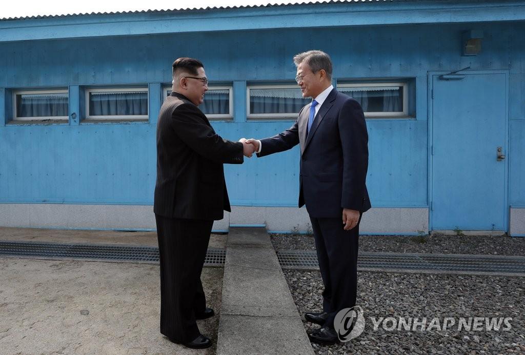 资料图片:2018年4月27日,在板门店军事分界线,韩国总统文在寅(右)和金正恩握手合影。(韩联社)
