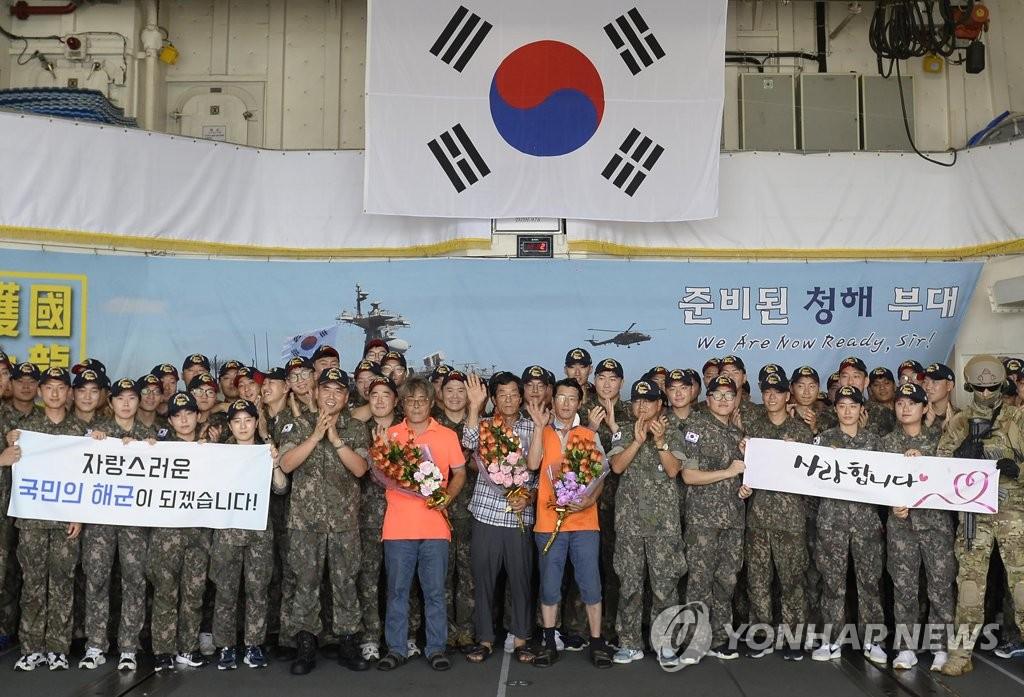"""资料图片:当地时间4月29日,获释的三名韩国公民在""""文武大王""""舰上合影留念。(韩联社/青瓦台提供)"""
