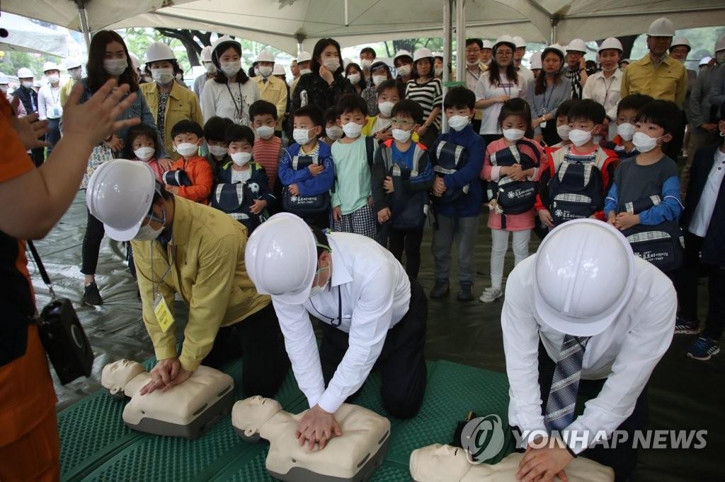 5月16日下午,在中央政府首尔办公大楼,参加演练的公务员正在演示心肺复苏急救法。(韩联社)
