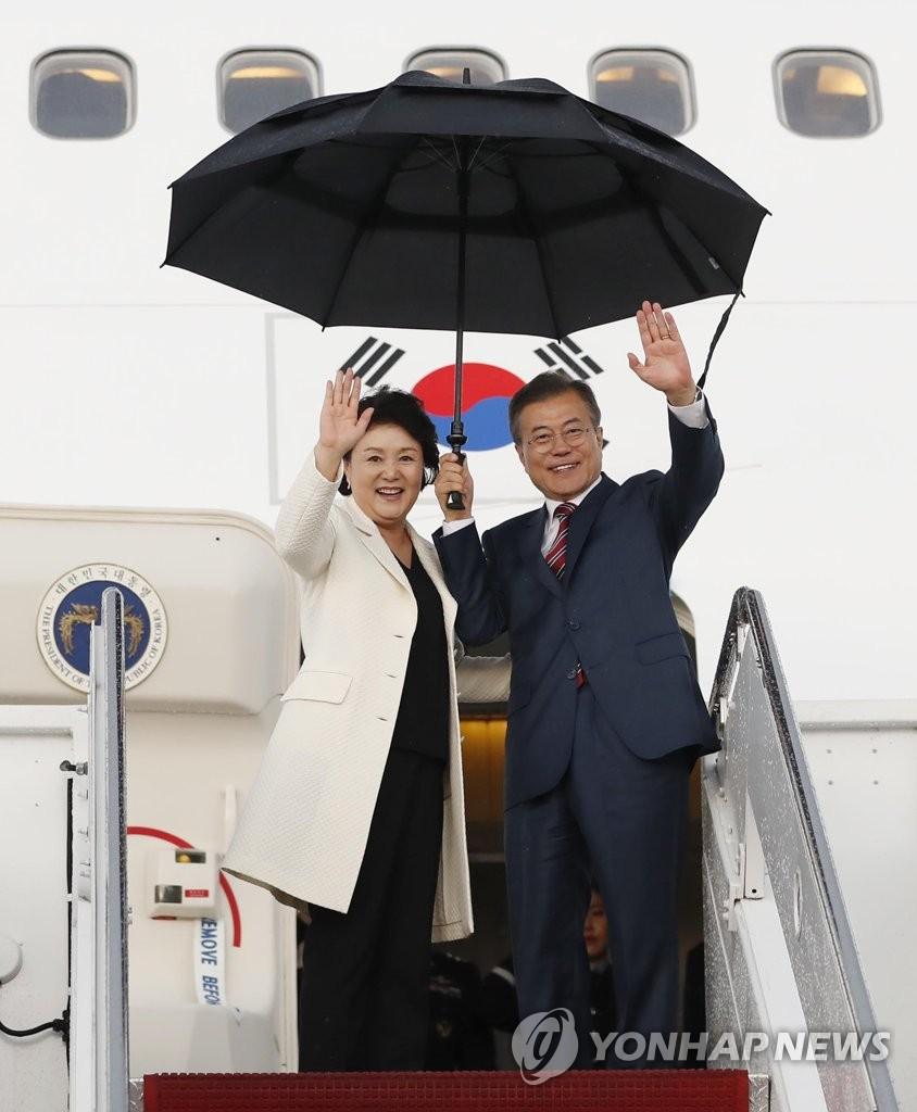 当地时间5月22日下午,在美国华盛顿安德鲁空军基地,结束对美国的访问启程回国的韩国总统文在寅(右)与夫人金正淑在机舱口向前来送行的人士挥手致意。(韩联社)