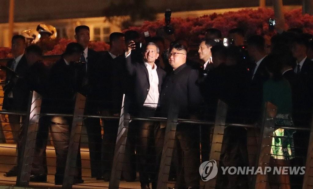当地时间6月11日晚,金正恩访问新加坡滨海艺术中心,与新加坡外长维文(左)合影留念。(韩联社)