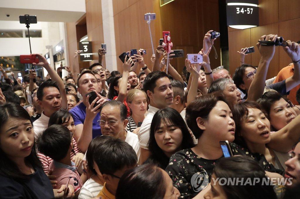 当地时间6月11日晚,在新加坡滨海湾金沙酒店,当地市民和游客纷纷用手机拍下夜游中的金正恩。(韩联社/欧新社)