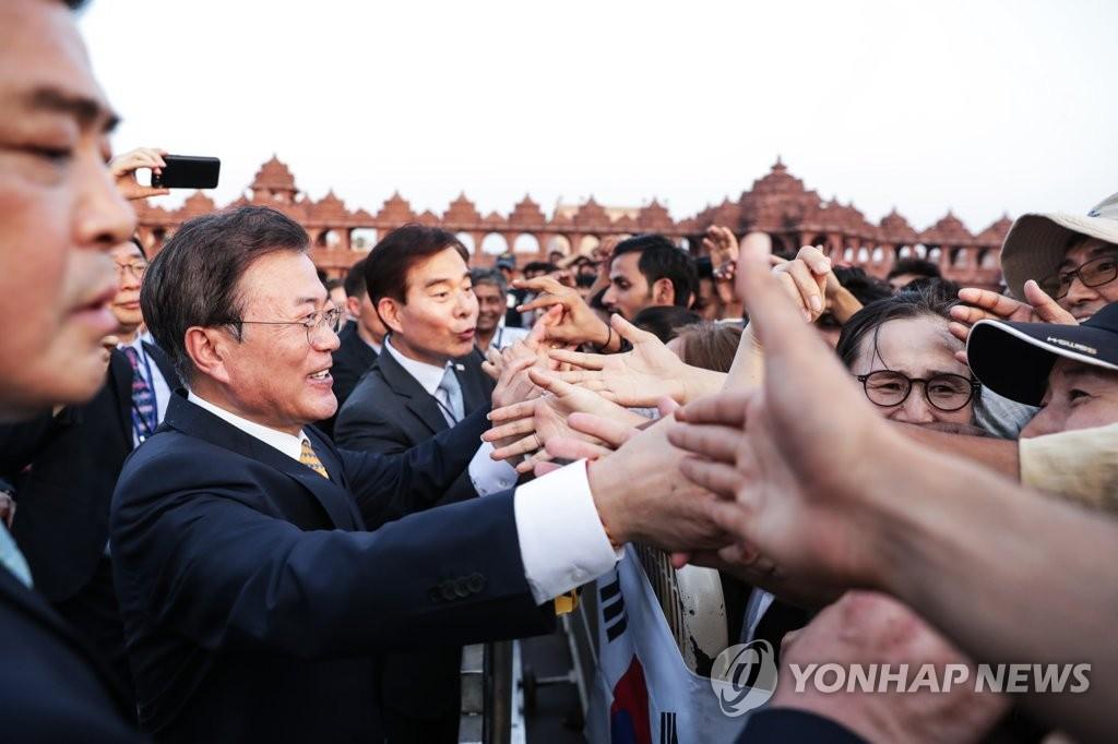 当地时间7月8日下午,在印度新德里,文在寅访问阿克萨达姆神庙。图为文在寅与到场等候的旅印侨胞握手致意。(韩联社)