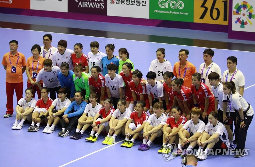 资料图片:8月14日,在雅加达,韩国队(白色球衣)和朝鲜队(红色球衣)选手在2018雅加达亚运会女子手球预赛前合影留念。(韩联社)