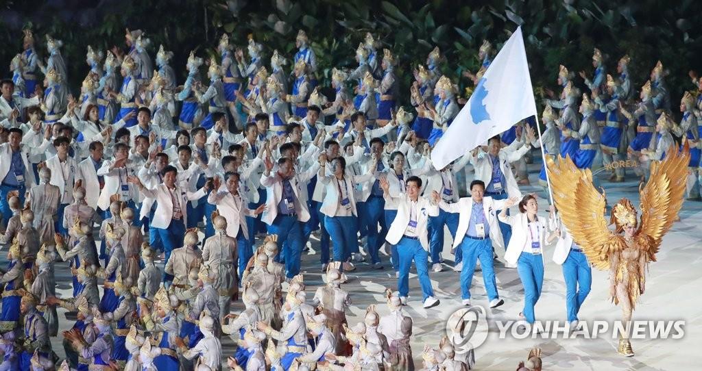 8月18日,在2018雅加达亚运会开幕式上,韩朝代表团举韩半岛旗共同入场。(韩联社)