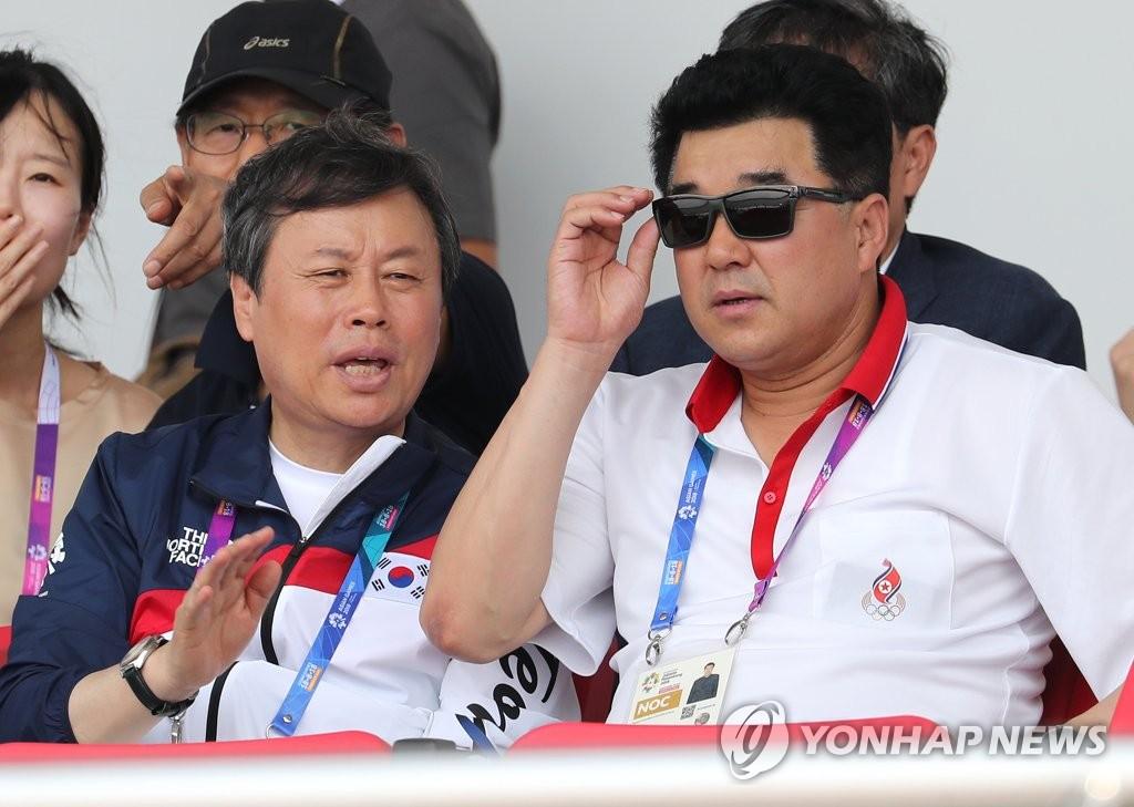 资料图片:8月22日上午,在印尼巨港,韩国文体部长都钟焕(左)和朝鲜体育相金一国(右)在观看韩朝赛艇联队的比赛。(韩联社)
