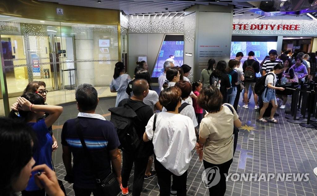 资料图片:中国游客等待进入韩国免税店。(韩联社)