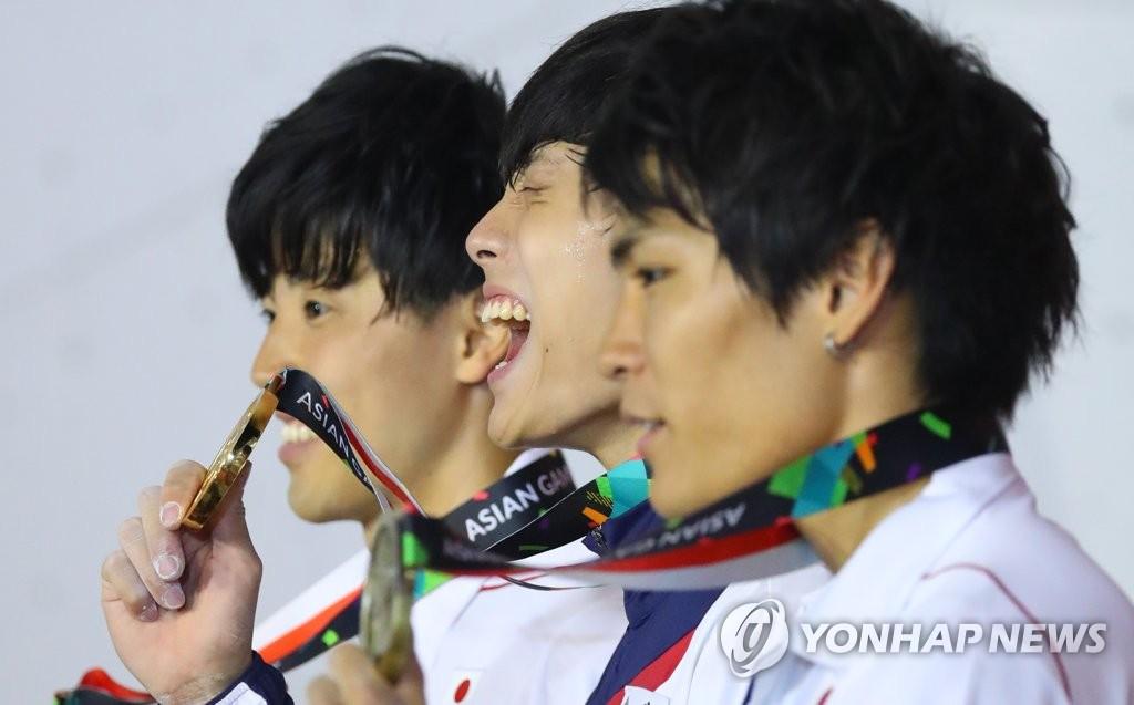 8月26日,在雅加达亚运会上,韩国选手千钟元(音,中)在夺得攀岩男子全能金牌后在领奖台上高喊韩国加油。(韩联社)