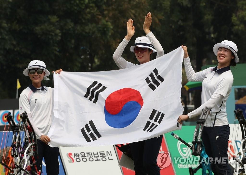 8月28日下午,在2018雅加达亚运会射箭女子团体复合弓决赛结束后,摘金的韩国队举太极旗庆祝胜利。(韩联社)