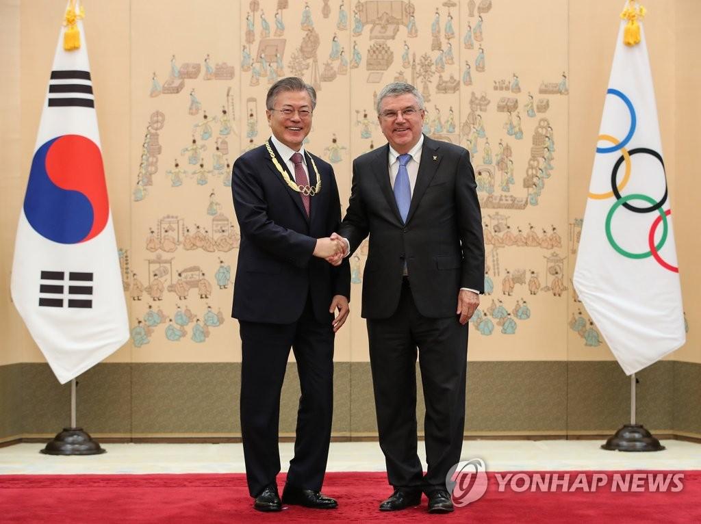 8月30日下午,在青瓦台,获颁奥林匹克金质勋章的韩国总统文在寅(左)与国际奥委会主席托马斯·巴赫握手合影。(韩联社)