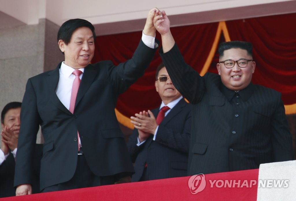 9月9日,在平壤金日成广场,金正恩(右)和栗战书牵手阅兵。(韩联社/欧新社)