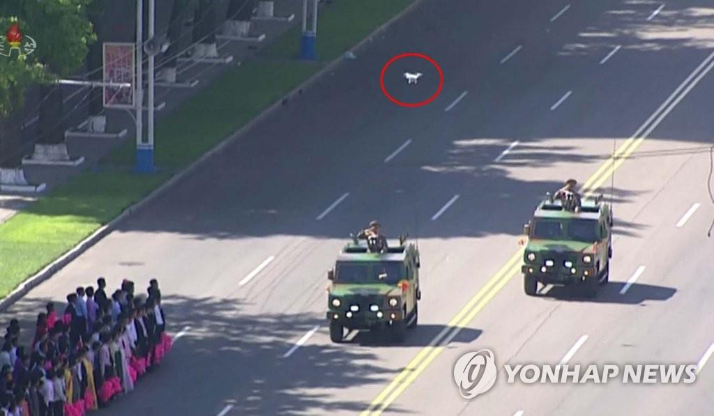 资料图片:朝鲜中央电视台从9月10日播出了时长2小时10分的建政70周年阅兵式录像。图为朝媒利用无人机(红圈)对阅兵式进行拍摄。图片仅限韩国国内使用,严禁转载复制。(韩联社/朝鲜央视)