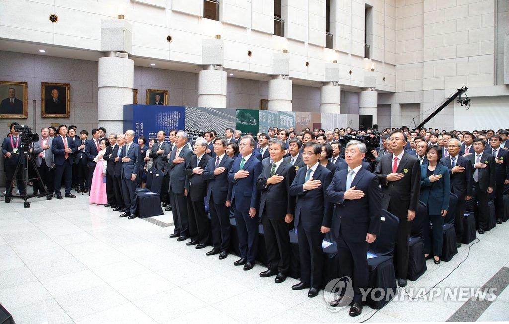 9月16日上午,韩国大法院中央大厅,韩总统文在寅(前排右四)、大法院长金命洙(右三)、宪法法院长李镇盛(右五)等人在向国旗敬礼。(韩联社)