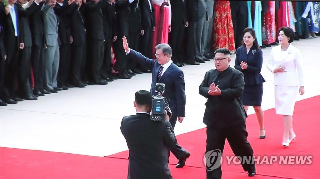 9月18日,在平壤顺安机场,文在寅(前排左)向前来欢迎的人员挥手致意。(韩联社/文金会主新闻中心直播画面)