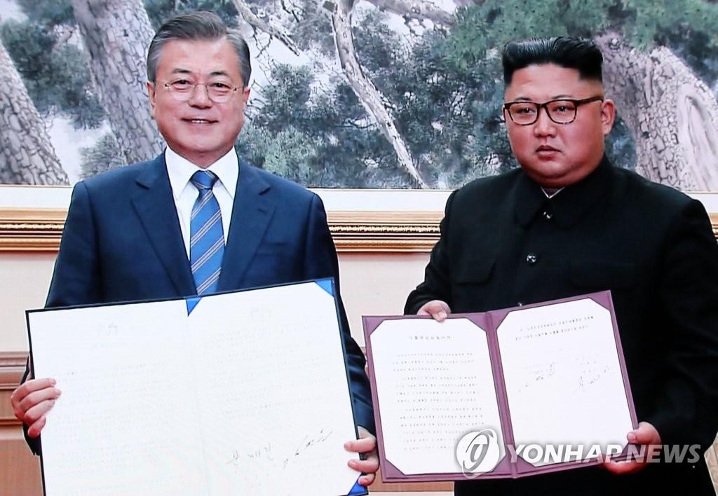 9月19日上午,在平壤百花园迎宾馆,韩国总统文在寅(左)和朝鲜国务委员会委员长金正恩签署《平壤共同宣言》后合影。图为首尔韩朝首脑会谈主新闻中心报道画面截图。(韩联社)