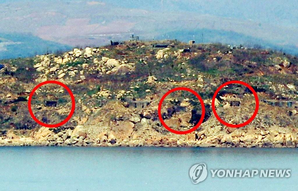 资料图片:4月25日从仁川市瓮津郡延坪面望乡瞭望台眺望到的朝鲜长在岛,岛上炮门(红圈)被关闭。(韩联社)