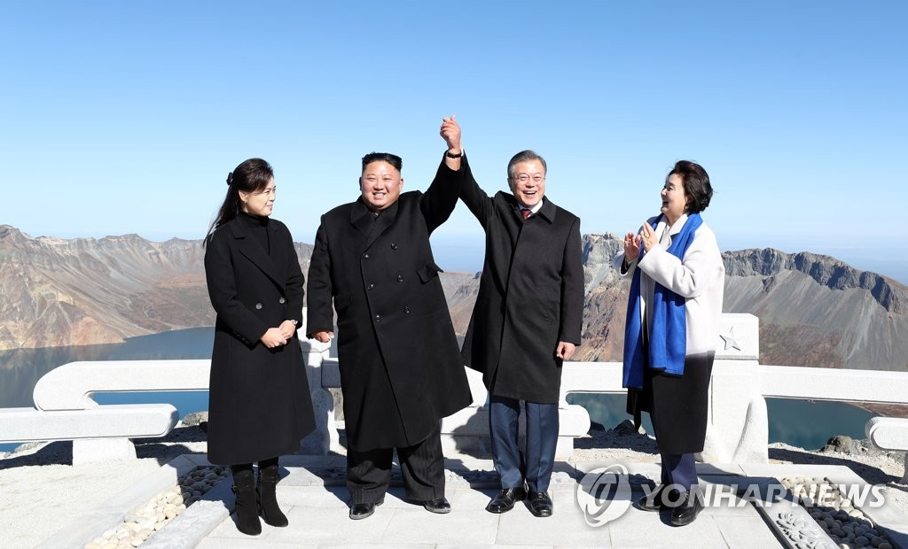 9月20日,在白头山将军峰,文在寅(右二)和金正恩(左二)牵手合影。(韩联社)