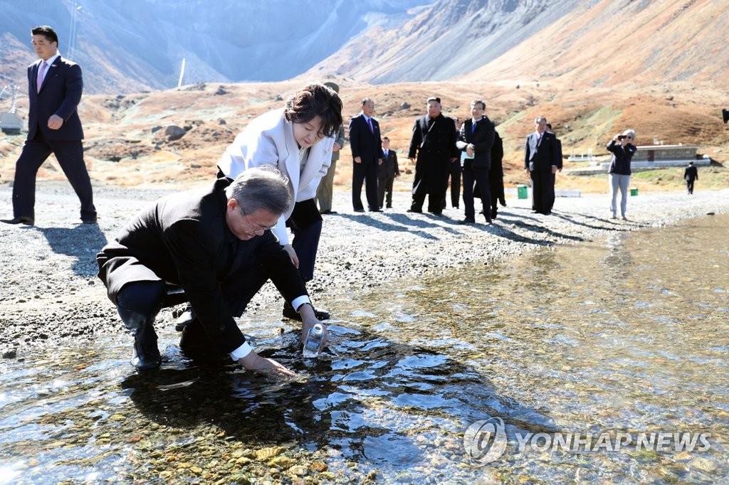 9月20日,在白头山天池边,文在寅将天池水装入瓶中。(韩联社)