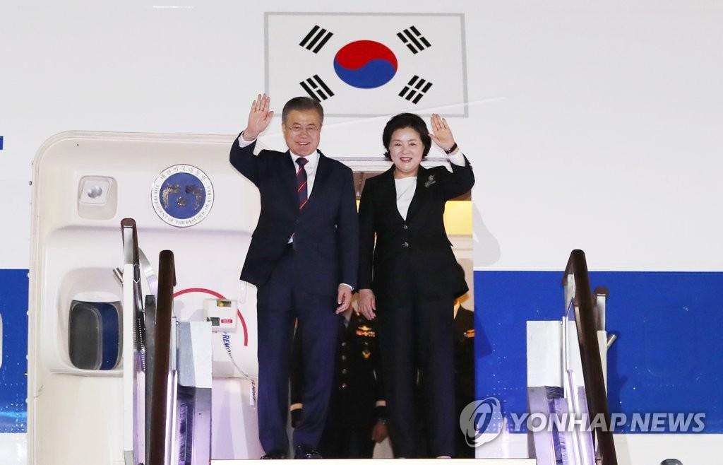 9月27日下午,在位于京畿道城南市的首尔机场,韩国总统文在寅(左)和夫人金正淑女士在舷梯口向前来迎接的人群挥手致意。(韩联社)