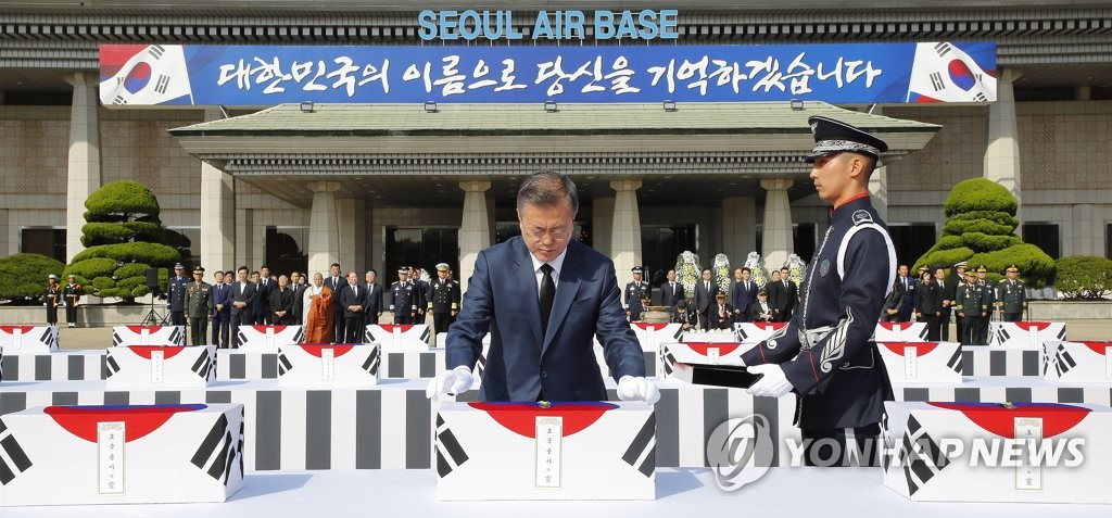 10月1日上午,在首尔机场举行的韩军遗骸归国仪式上,文在寅向64位烈士授予参战纪念章。(韩联社)
