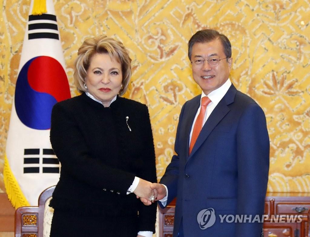 10月5日下午,在青瓦台,韩国总统文在寅(右)与到访的俄罗斯联邦委员会主席瓦伦缇娜·伊万诺夫娃·马特维延科握手。(韩联社)