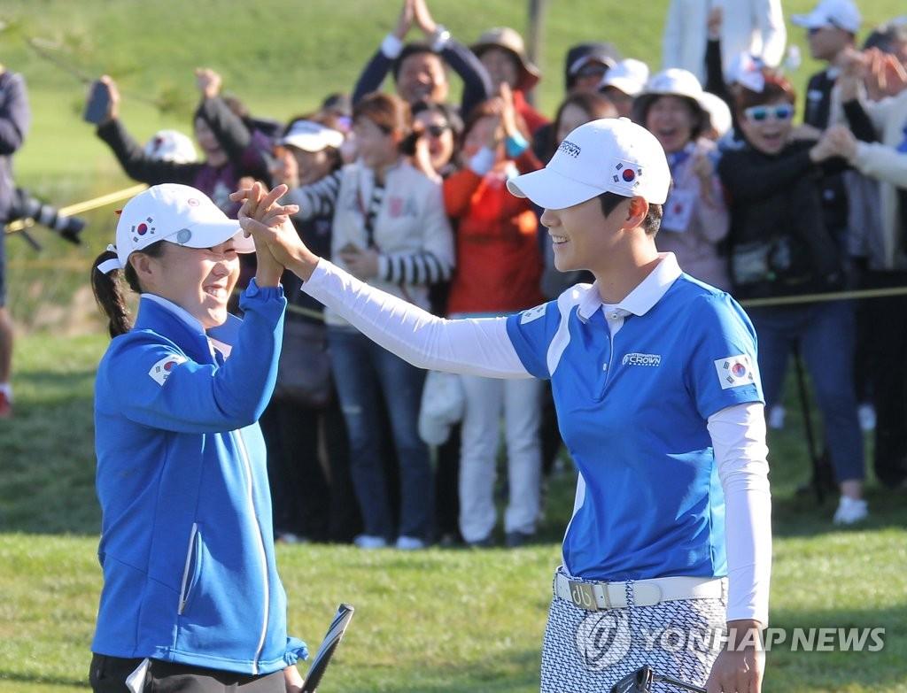 10月7日,在韩国仁川杰克·尼克劳斯高尔夫俱乐部,朴城炫(右)在第13洞成功抓小鸟后与金寅敬击掌庆祝。(韩联社/UL国际皇冠杯组委会供图)