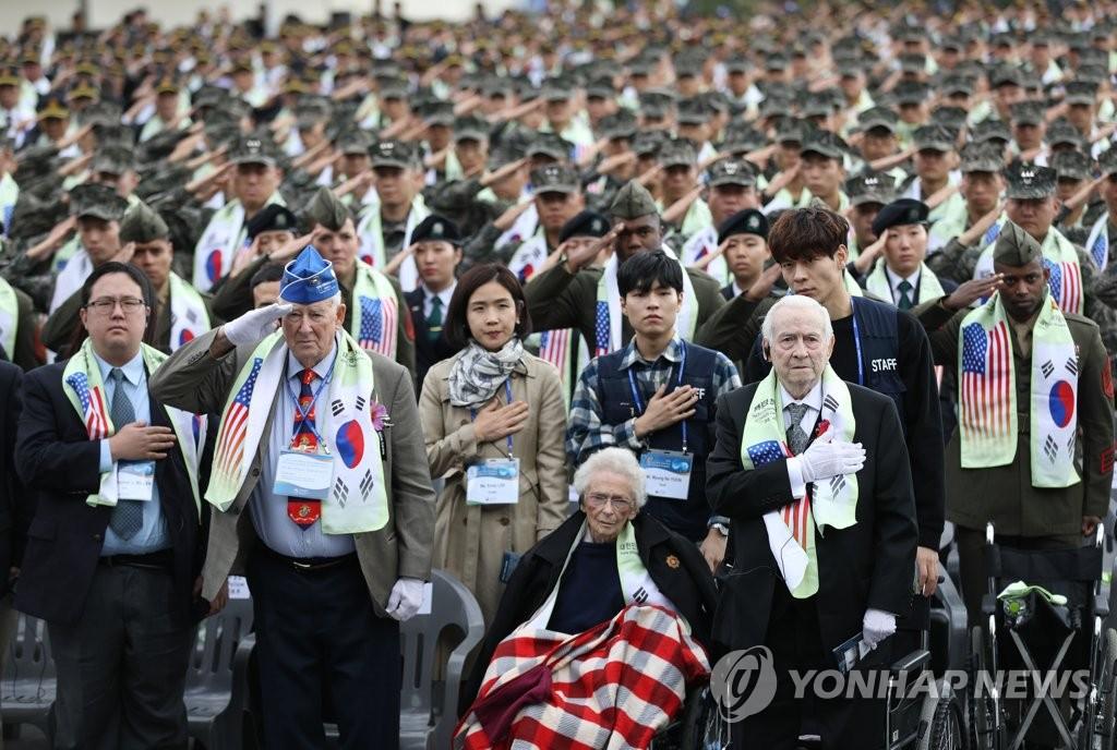 10月10日下午,第3次长津湖战役英雄追悼活动在首尔龙山战争纪念馆举行。图为参战勇士詹姆斯·伍德(前排右一)和罗伯特·佩洛(前排右三)等与会者向国旗致敬。韩联社