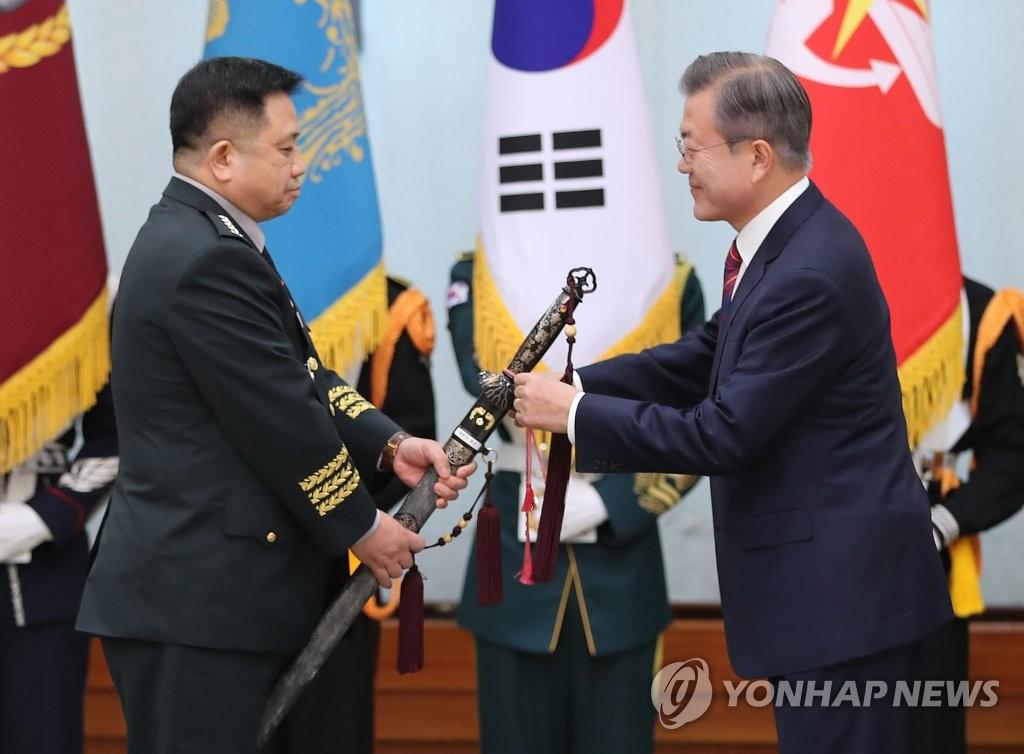10月12日上午,在青瓦台,韩国总统文在寅出席韩军将军晋级及就任仪式并向新任联参议长朴汉基授予三精剑。(韩联社)