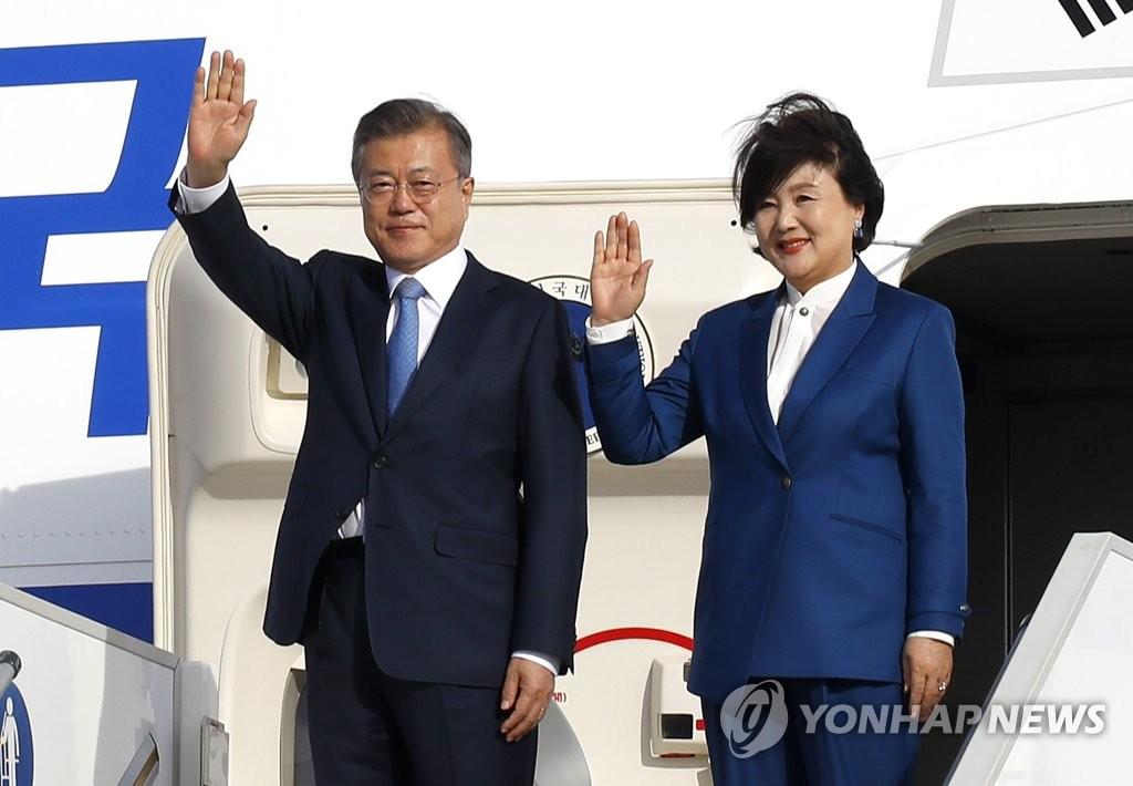 当地时间10月13日下午,韩国总统文在寅(左)和夫人金正淑飞抵法国巴黎奥利机场,向接机人员挥手致意。(韩联社)