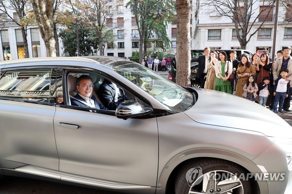 """当地时间10月14日下午,在法国巴黎香榭丽舍大道附近,韩国总统文在寅乘坐现代汽车旗下氢燃料电池车型""""NEXO""""游览巴黎市区。文在寅乘坐的是现代汽车首辆出口至法国的NEXO。(韩联社)"""