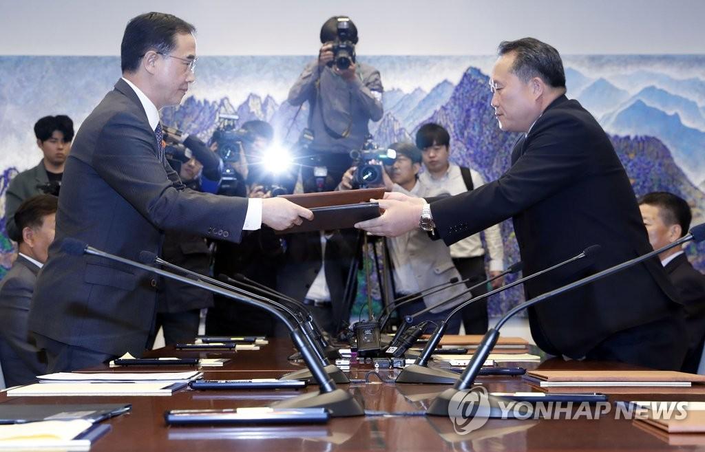 10月15日,在板门店,韩朝高级别会谈韩方首席代表、统一部长官赵明均(左)同朝方首席代表、祖国和平统一委员会首席代表、祖国和平统一委员会委员长李善权在会后交换联合公报。(韩联社/韩媒联合采访团)
