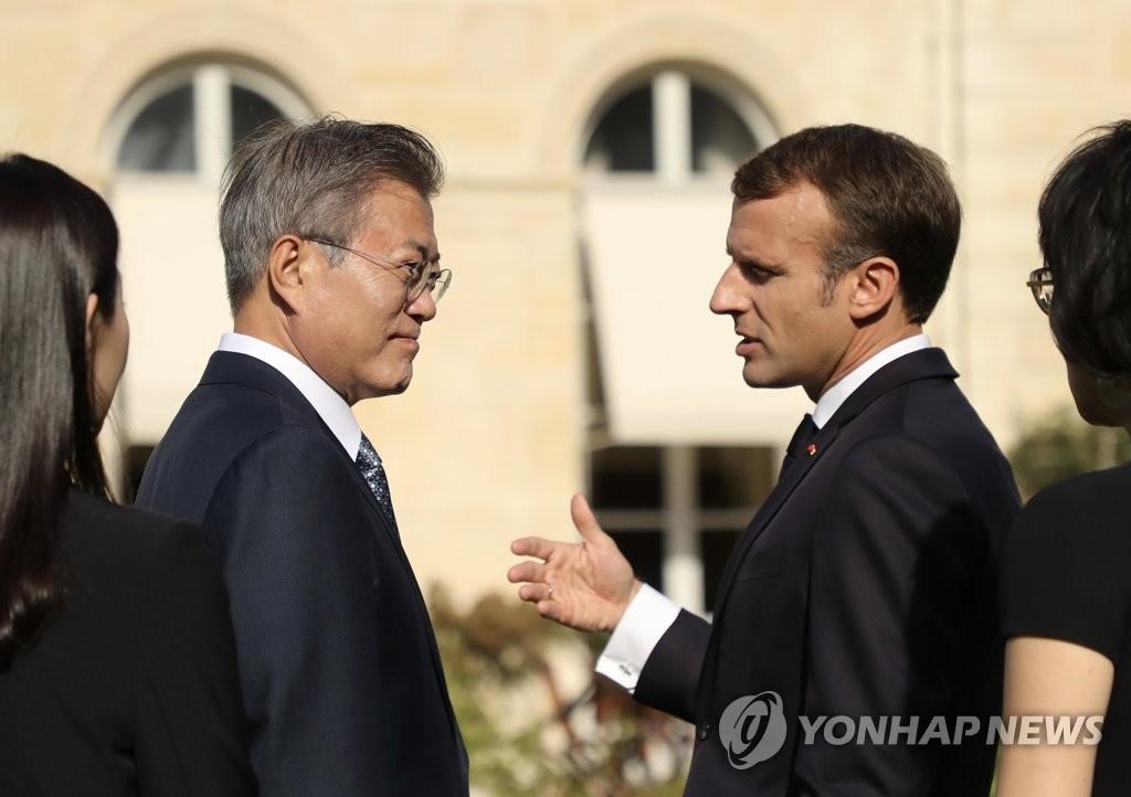 当地时间10月15日,在法国巴黎,韩国总统文在寅(左)和法国总统马克龙亲切交谈。(韩联社)
