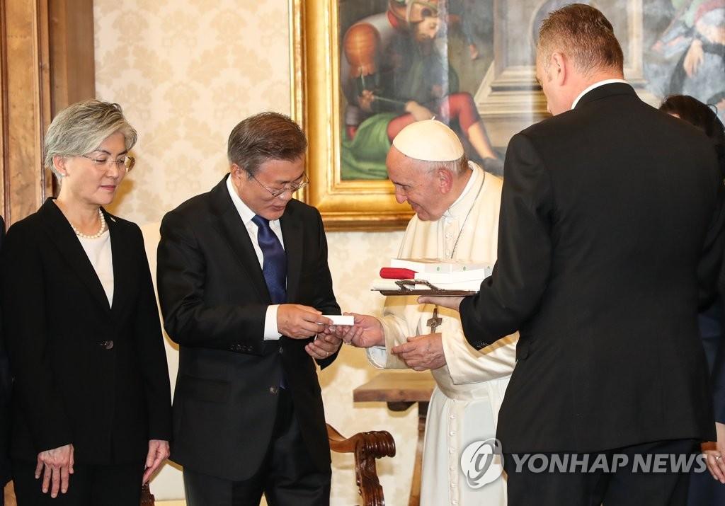 当地时间10月18日,在罗马教廷,韩国总统文在寅(左二)从教皇方济各(右二)手中接过方济各作为礼物赠送的圣珠。(韩联社)