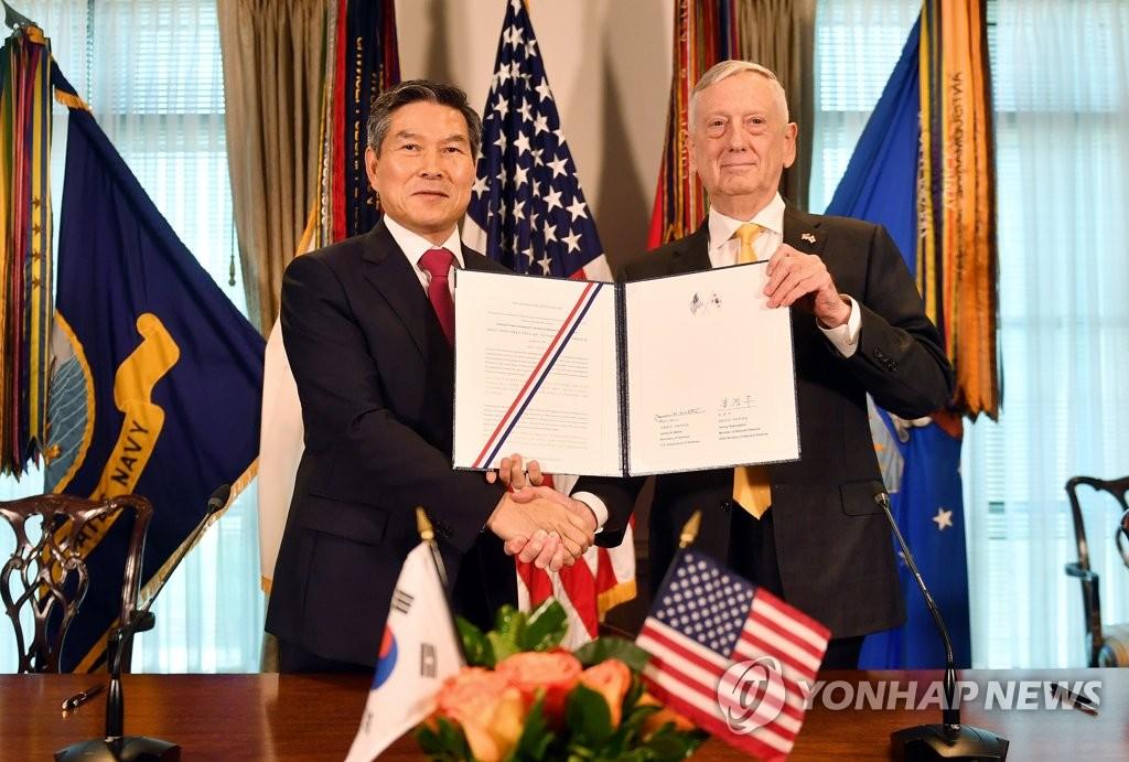 """郑景斗(右)和马蒂斯签署""""战权移交后防卫合作指针""""后握手合影。(韩联社/国防部供图)"""