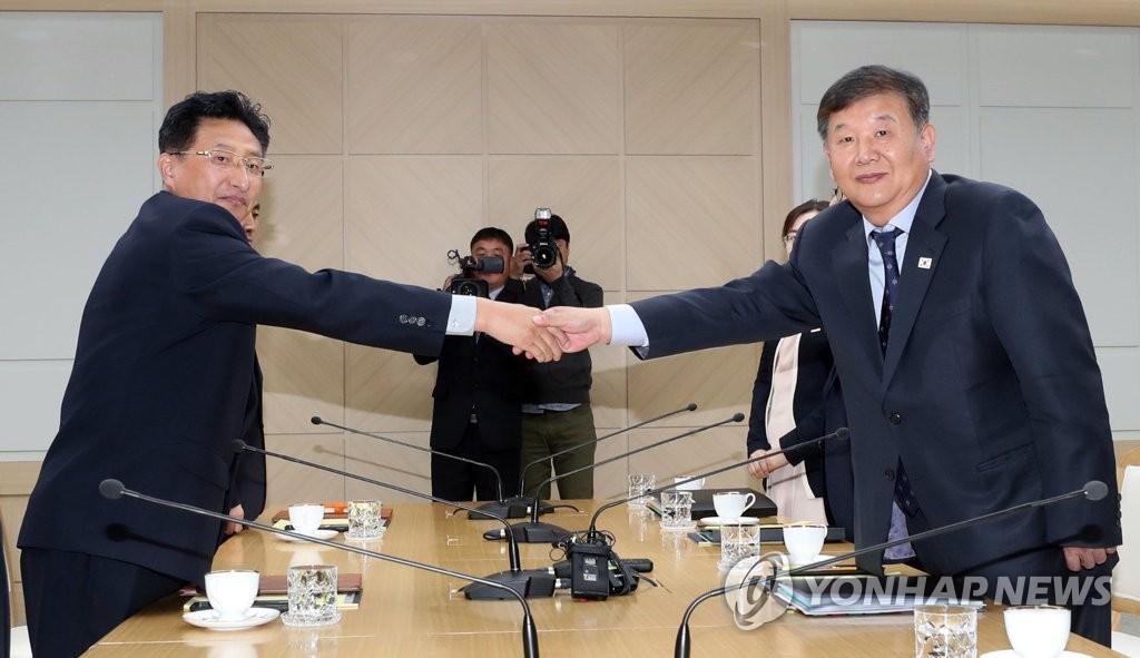11月2日,在朝鲜开城市的韩朝联络办公室,韩朝举行体育会谈。卢泰刚(右)和元吉友在会上握手。(韩联社/联合采访团)
