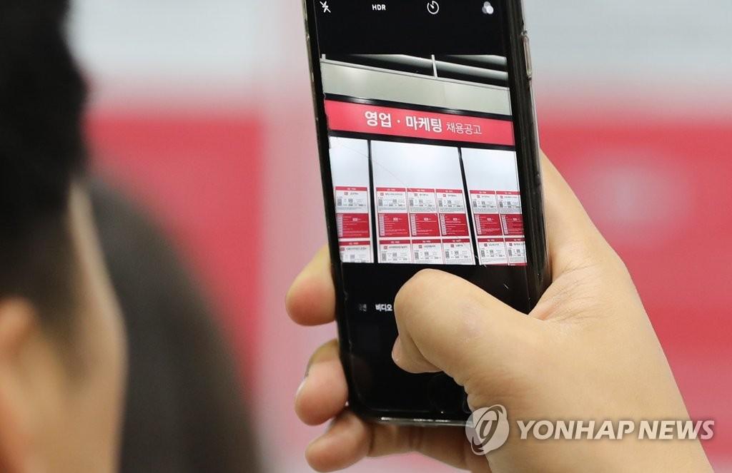 """资料图片:图为2018年11月12日在首尔瑞草区举行的""""2018三星(电子)合作公司招聘会""""上一位求职人员正用手机拍摄招聘公告。(韩联社)"""