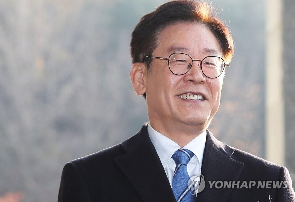 资料图片:11月19日上午,在水原市,李在明在京畿道政府大楼前面带微笑地答记者问。(韩联社)