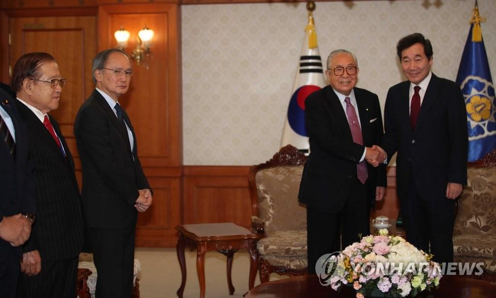 11月19日,在中央政府首尔大楼,韩国国务总理李洛渊(右一)同到访问的韩日日韩合作委员会代理委员长渡边秀央(右二)握手。(韩联社)