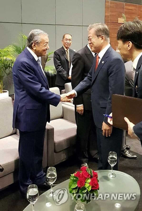 资料图片:2018年11月20日,正在新加坡和巴布亚新几内亚访问的韩国总统文在寅(右)和马来西亚总理马哈蒂尔握手。(韩联社/青瓦台供图)