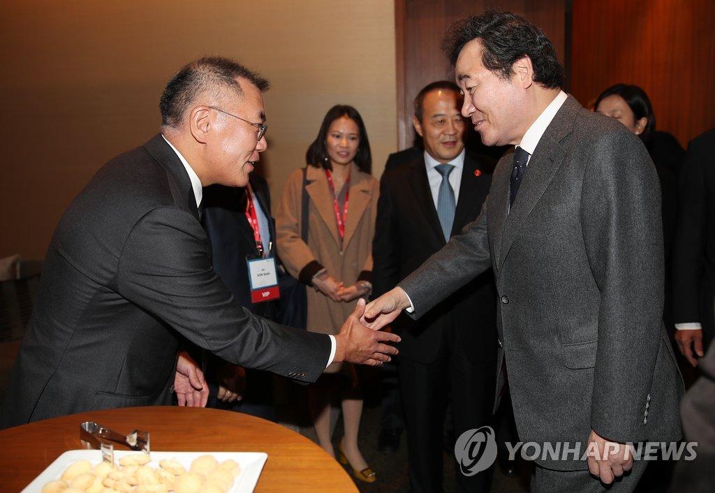 11月20日,在首尔新罗酒店,韩国国务总理李洛渊(右)同现代汽车集团副会长郑义宣(左)在出席博鳌亚洲论坛首尔会议开幕式前握手合影。(韩联社)